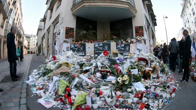Des fleurs et des bougies sont déposées devant les locaux de Charlie Hebdo à Paris en hommage aux victimes de l'attentat, le 11 janvier 2015 [Joël SAGET / AFP/Archives]