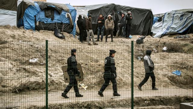 """Des CRS en patrouille devant le camp de migrants """"la Jungle"""" le 21 février à Calais  [PHILIPPE HUGUEN / AFP/Archives]"""