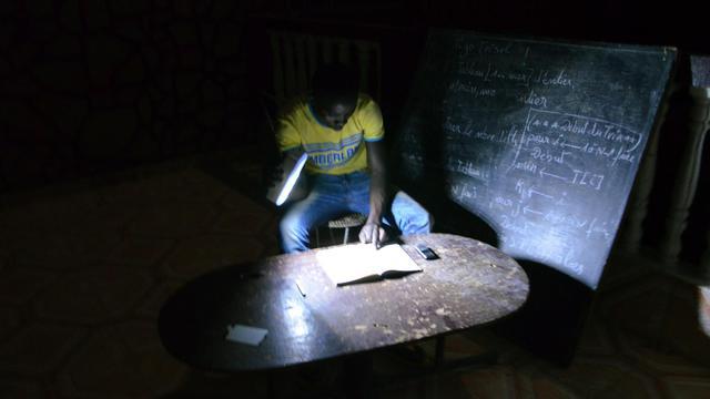 Un étudiant révise ses cours à la lueur d'une lampe de poche à Niamey, le 18 juin 2013 [Boureima Hama / AFP]