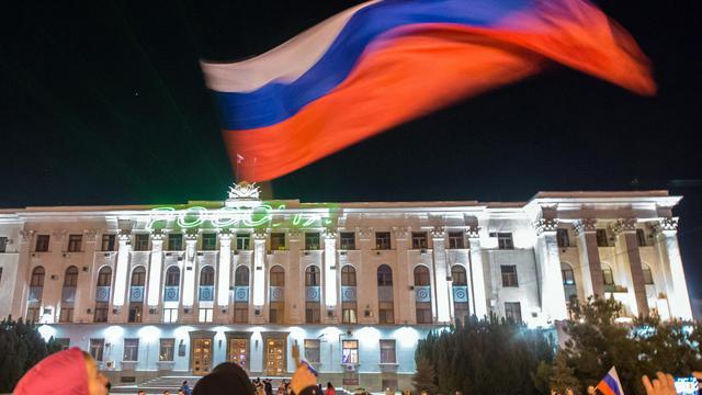 """Un homme brandit un drapeau russe tandis que le mot """"Russie"""" est projeté sur un immeuble du centre de Simferopol, en Crimée, le 21 mars 2014 [Dmitry Serebryakov / AFP/Archives]"""