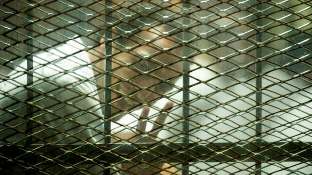 """Le photojournaliste égyptien Mahmoud Abu Zeid """"Shawkan"""" fait le V de la victoire dans le box des accusés devant les journalistes au tribubal au Caire le 8 septembre 2018 [Mohamed el-Shahed / AFP]"""