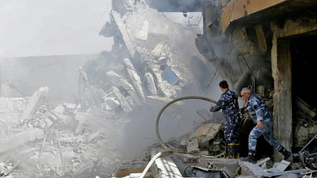 Des soldats syriens inspectent un centre de recherches dans le nord de Damas visé par des frappes américaines, françaises et russes en représailles à une attaque chimique présumée le 14 avril 2018 [LOUAI BESHARA / AFP]