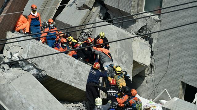 Des secouristes recherchent des survivants dans les décombres d'un immeuble le 7 février 2016, à Tainan, dans le sud de Taïwan, au lendemain d'un séisme de magnitude 6,4 [SAM YEH / AFP]