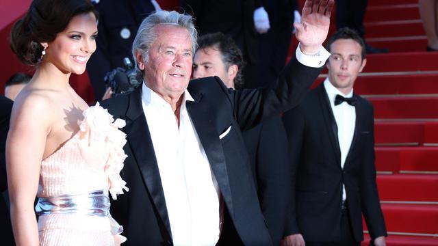 """Le comédien français Alain Delon (d) le 26 mai 2013 à la 66e édition du festival de Cannes aux côtés de Marine Lorphelin pour la projection du film """"Zulu""""  [Loic Venance / AFP/Archives]"""
