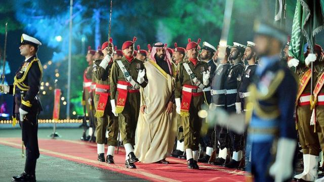 Photographie prise et diffusée le 17 février 2019 par le Département de l'information du Pakistan (PID) montrant le prince héritier saoudien Mohammed ben Salmane (C) accueilli par une garde d'honneur chez le Premier ministre à Islamabad [HANDOUT / PID/AFP]