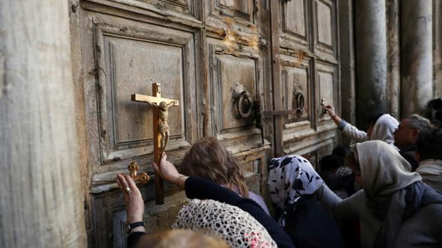 Des fidèles prient le 27 février 2018 devant le Saint-Sépulcre, lieu le plus saint du christianisme à Jérusalem, après sa fermeture dimanche [Thomas COEX / AFP]
