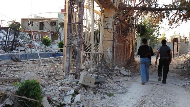 Des rebelles marchent dans les ruines d'immeubles de Mleiha le 25 juillet 2013 [- / Shaam News Network/AFP/Archives]