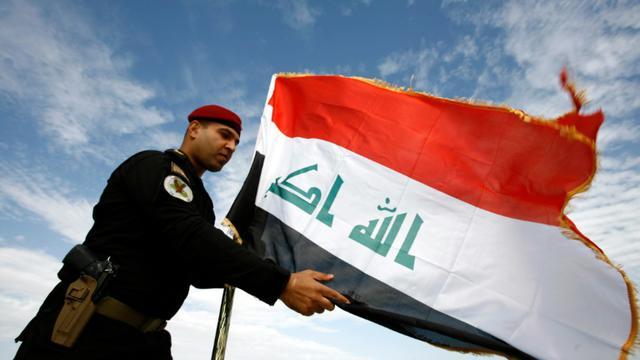 Un policier irakien devant le drapeau de l'Irak, à Najaf le 9 janvier 2016 [HAIDAR HAMDANI / AFP/Archives]
