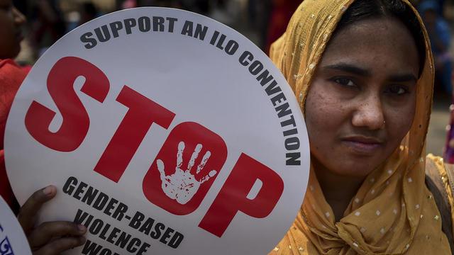 Une femme bangladaise descendu dans la rue pour réclamer des conditions de vie plus sûres pour les femmes du pays, tient une affiche alors qu'elle participe à un rassemblement pour souligner la Journée internationale de la femme à Dhaka, le 8 mars 2019.
