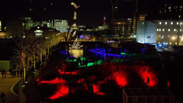 """Au loin, """"Diver"""" (""""Le plongeur"""") par l'artiste britannique Ron Haselden, une des 30 installations artistiques lumineuses qui célèbrent Londres """"by night"""", pour sa première fête des Lumières, le 14 janvier 2016. [JUSTIN TALLIS / AFP]"""