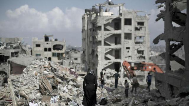 Une femme palestinienne marche au milieu de ruines près de Gaza City, le 6 août 2014.