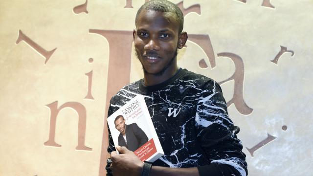 """Lassana Bathily pose avec son livre """"Je ne suis pas un héros"""", le 16 décembre 2015, à Paris."""