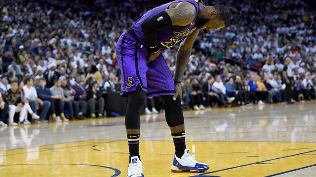 LeBron James, n°23 des Lakers de Los Angeles, se tord de douleur après avoir été blessé contre les Golden State Warriors lors de la deuxième moitié de leur match de NBA à l'Oracle Arena le 25 décembre 2018 à Oakland, en Californie.