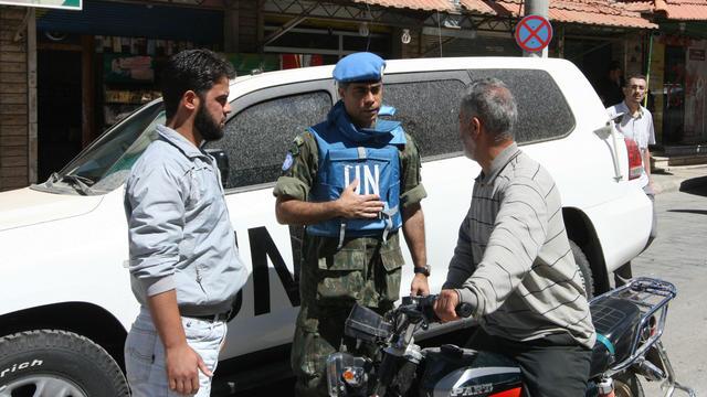 Un observateur de l'ONU parle à un habitant de la ville de Madaya, en Syrie, le 6 mai 2012.