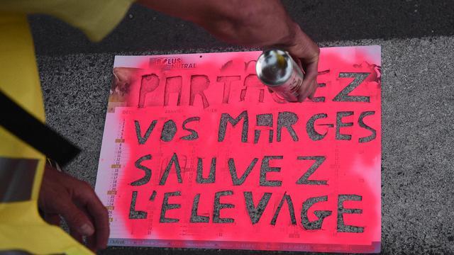 e5e9e414dcc Un agriculteur fabriquant une pancarte au pochoir sur laquelle est écrit