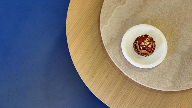 Une grande table d'hôte circulaire rassemble les visiteurs autour des pâtisseries.
