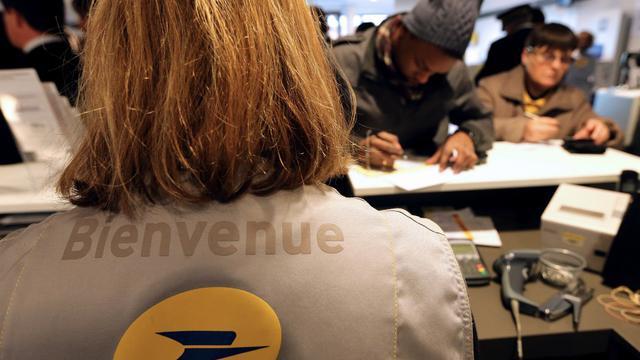 Des clients au guichet d'un bureau de poste à Reims.
