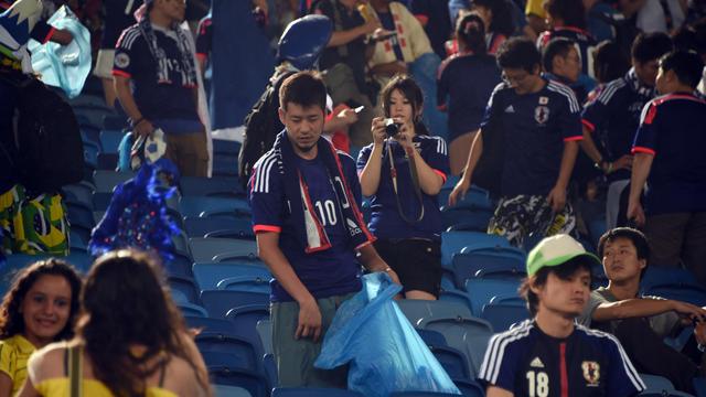 Les fans nippons nettoient les gradins à l'issue du match.