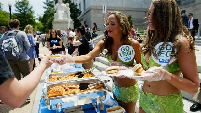 Des militantes de la PETA vêtues de feuilles de laitue distribuent des hot-dogs vegans.