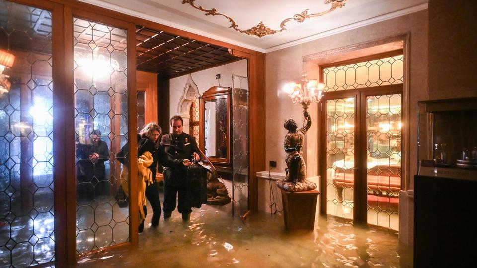 Des palaces centenaires ont été envahis par les eaux. Ici, un employé du Gritti Palace aide une cliente, le 12 novembre.