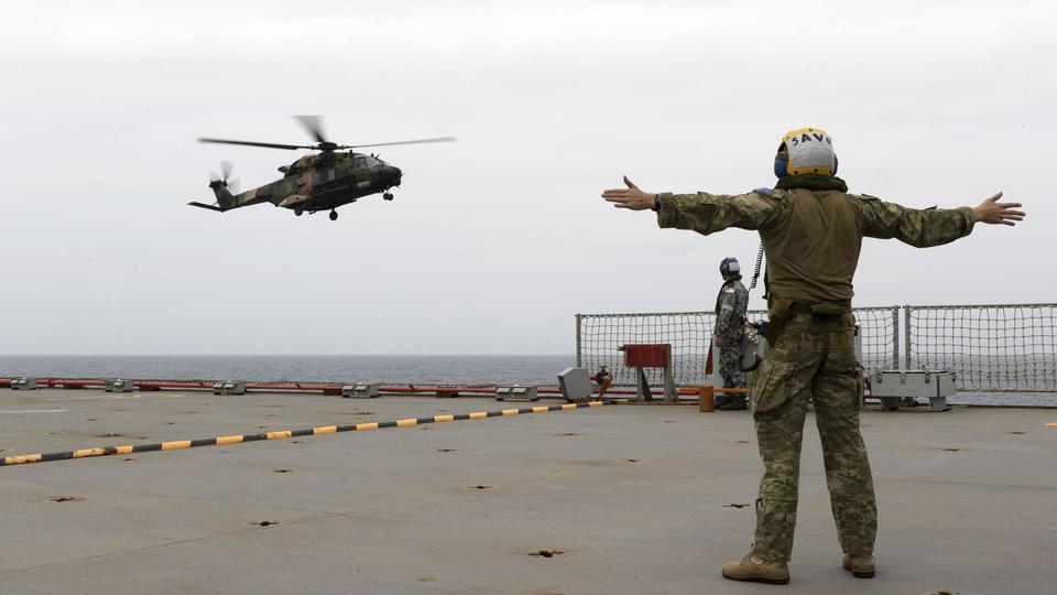 Un hélicoptère de l'armée australienne vole au-dessus d'un navire qui ira soutenir les communautés touchées par les incendies en Nouvelle-Galles du Sud.