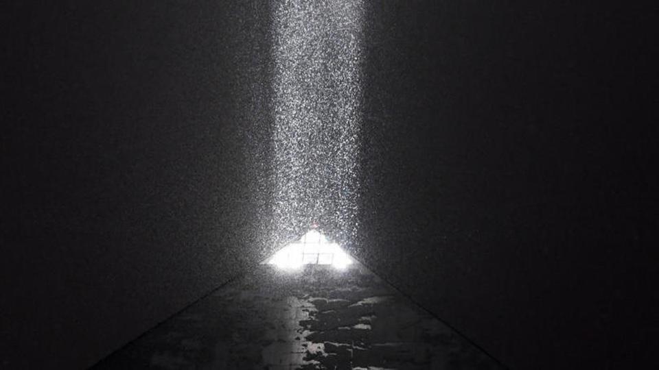 La lumière projetée par la pyramide de l'hôtel Louxor illumine les flocons qui tombent sur la ville.
