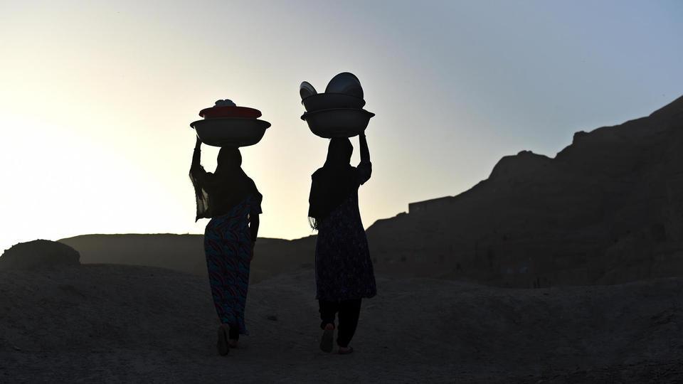 Deux Afghanes portent leur vaisselle sur leurs têtes dans la vieille ville de Bamiyan, en 2015.