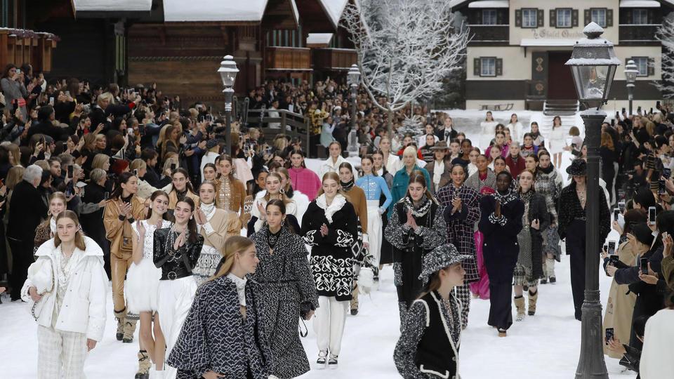 Le défilé-spectacle, sous la verrière du Grand palais, a débuté par une minute de silence. Face à un public nourri, les mannequins sont restés debout, silencieux, dans le décor d'une station de ski, avec flocons, chalets en bois et des skis tagués Chanel.