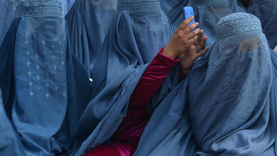 Une femme prend une photo pendant un meeting du candidat à la présidentielle Abdullah Abdullah, en 2014.